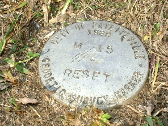 Close-up photo of a M-15 Reset geodetic survey marker on the ground (PDF)