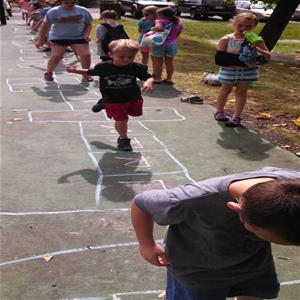 Campers play hopscotch on asphalt