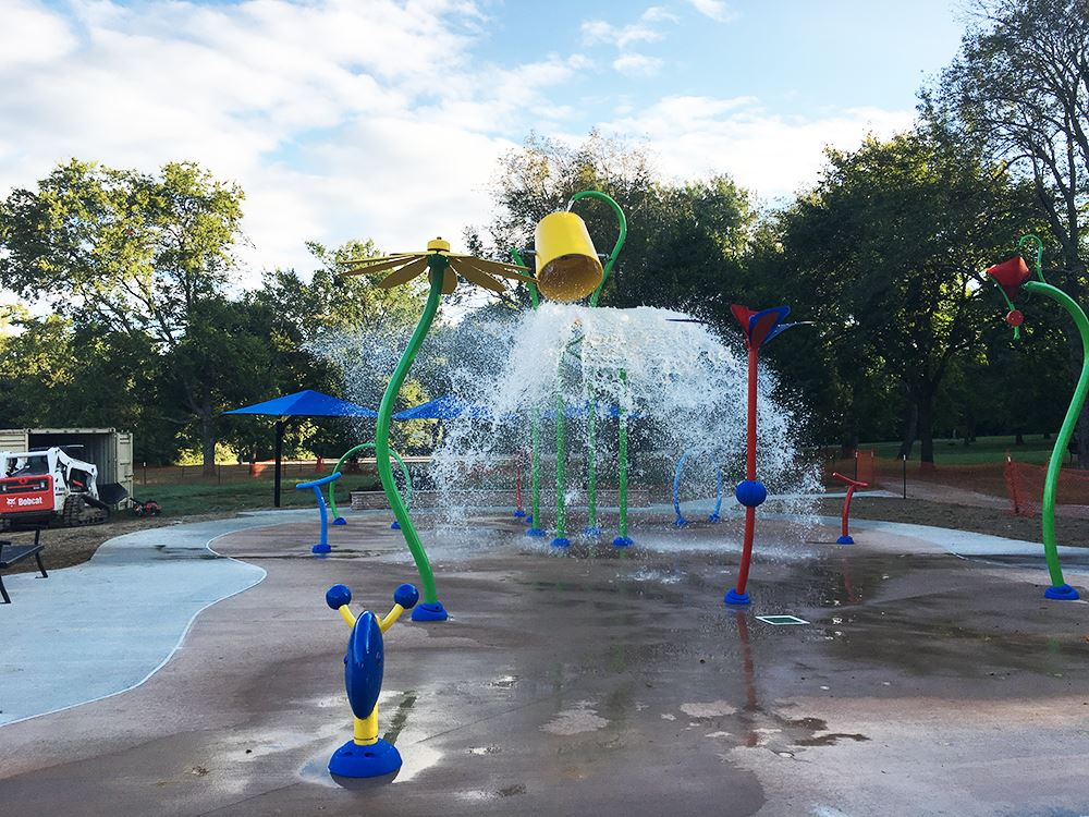 A large yellow bucket dumps water onto the newly constructed splash pad