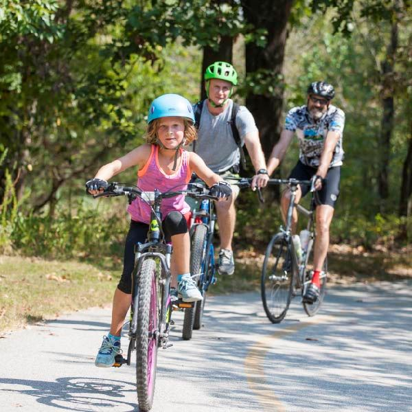 A family rides bikes toward the camera on Fayetteville trail.